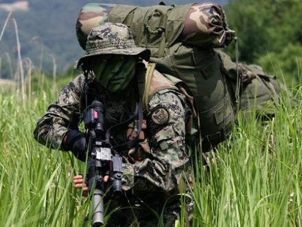 """Elemento das forças especiais sul-coreanas. A arma é uma pistola-metralhadora Daewoo K7, 9X19 mm. O chaebol (""""conglomerado"""") Daewoo é um conjunto de empresas sul-coreanas de mecânica pesada e alta tecnologia, criado em 1967 por Kim Woo Chong, capitalista local de porte médio, que recebeu fortes subsidios do governo militar da época. Não fabrica apenas carros feios, mas também armas feias."""